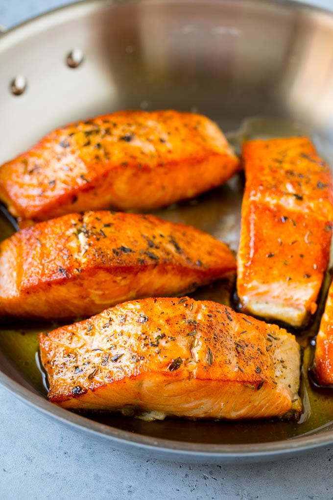 Seared salmon fillets in a skillet.