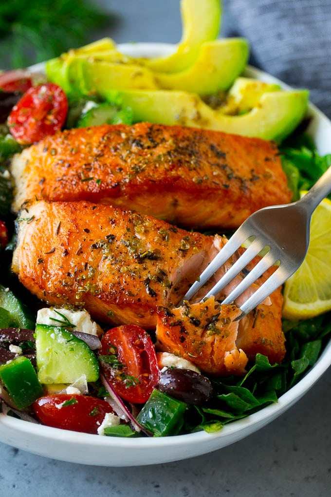 A fork cutting into a salmon fillet in Greek salmon salad.