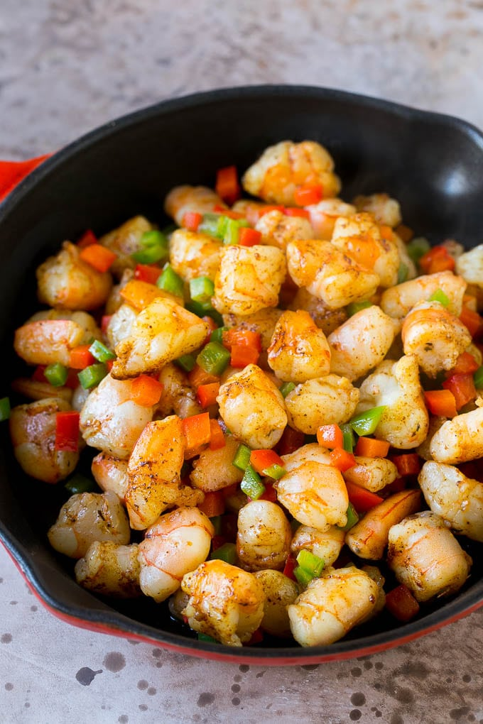 A skillet full of chopped shrimp and bell peppers.