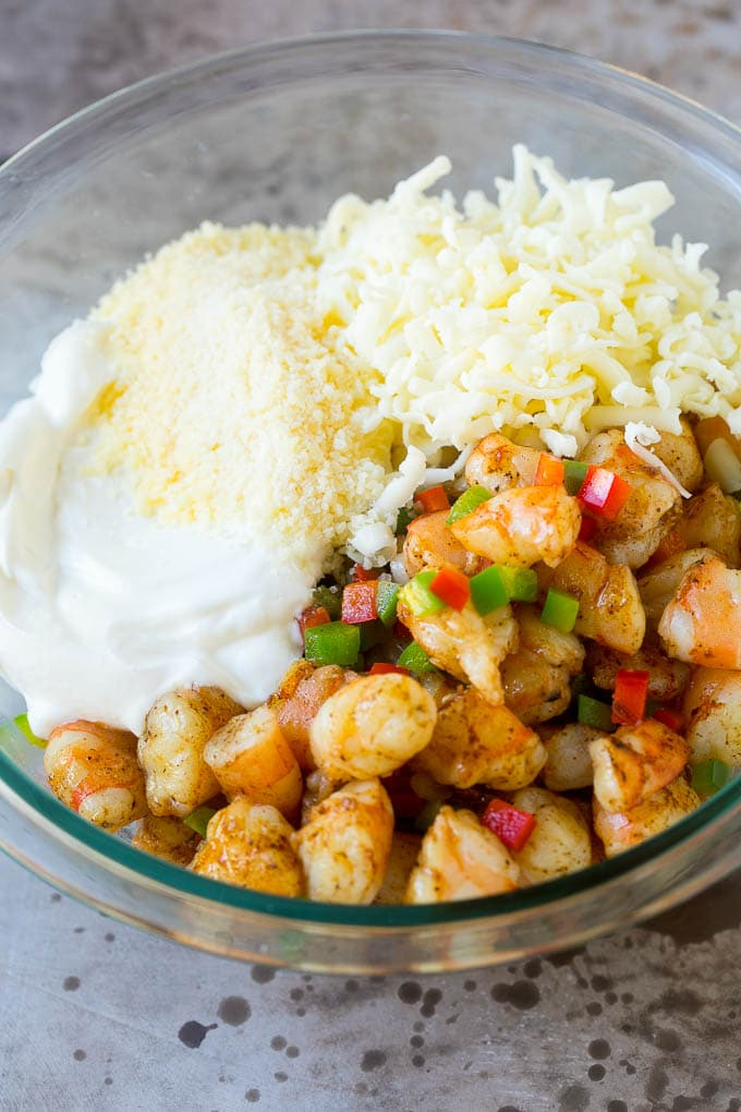 Chopped shrimp, peppers, cheese and sour cream in a bowl.