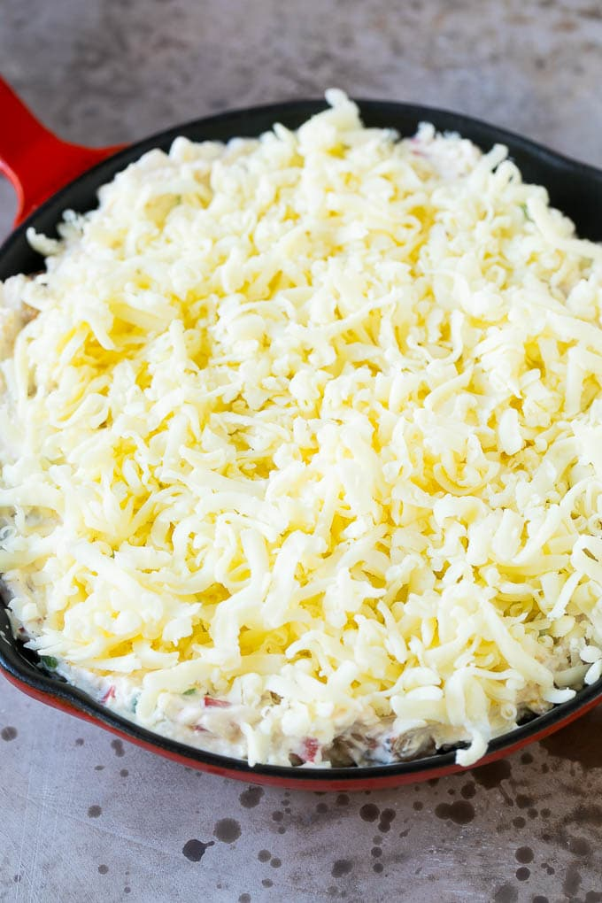 A skillet of shrimp dip topped with a layer of shredded cheese.
