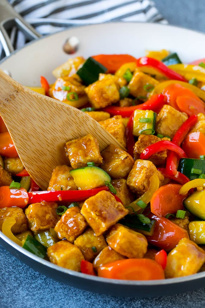 A p an of tofu stir fry with a spatula in it.