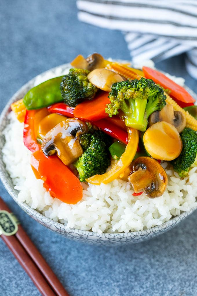 Vegetable stir fry served over rice in a bowl.