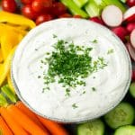 Veggie dip topped with fresh herbs and served with colorful vegetables.