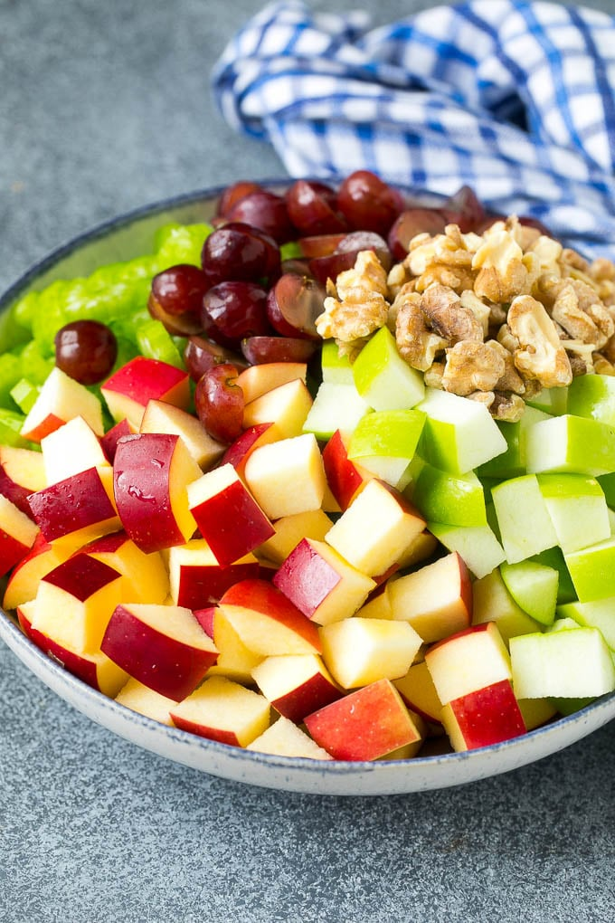 Red and green apples, grapes, walnuts and celery in a serving bowl.