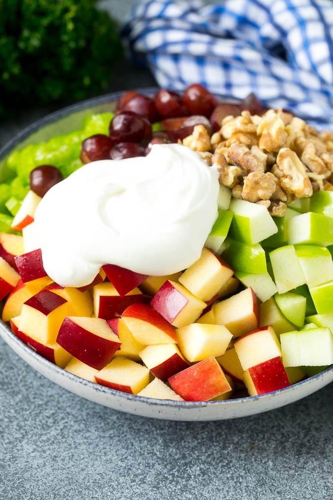 Apples, grapes, walnuts and celery in a bowl topped with creamy dressing.