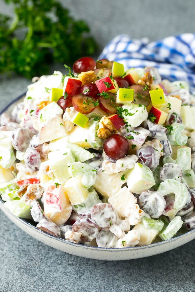 A bowl of Waldorf salad made with fruit, nuts and celery all tossed in a creamy dressing.