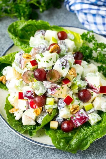 Waldorf salad with apples, grapes, celery and pecans, served on a bed of lettuce leaves.