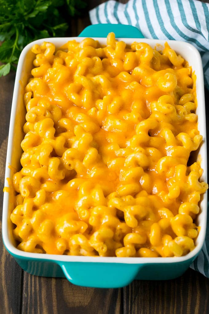 Baked mac and cheese in a blue casserole dish.