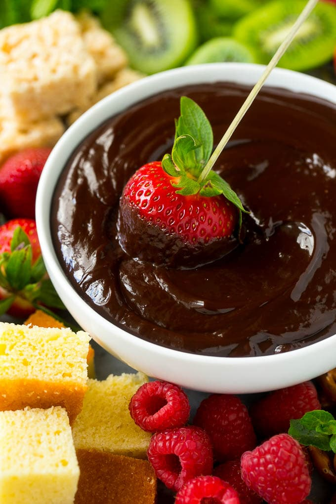 A strawberry on a skewer dipped into a bowl of chocolate fondue.