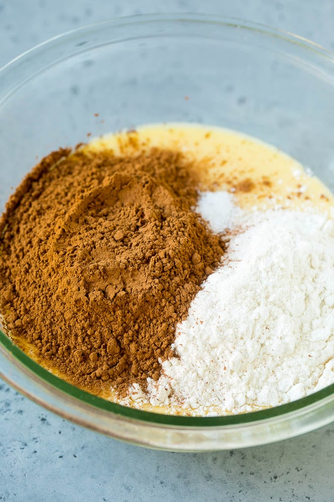 Cocoa powder and flour in a bowl of melted butter and sugar.