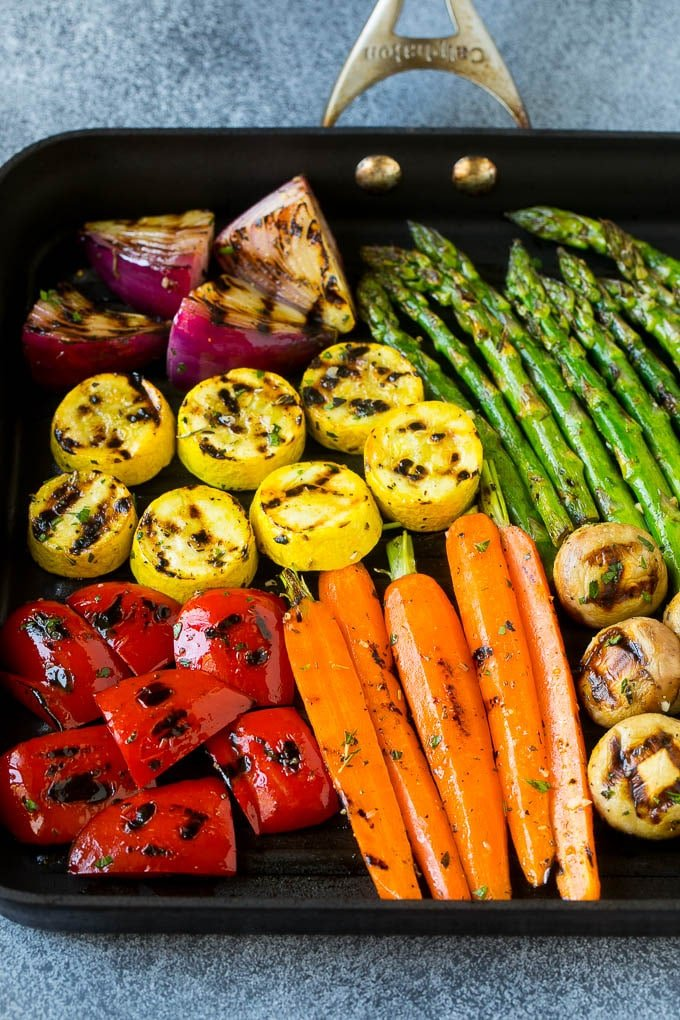 A grill pan with an assortment of vegetables cooking on it.