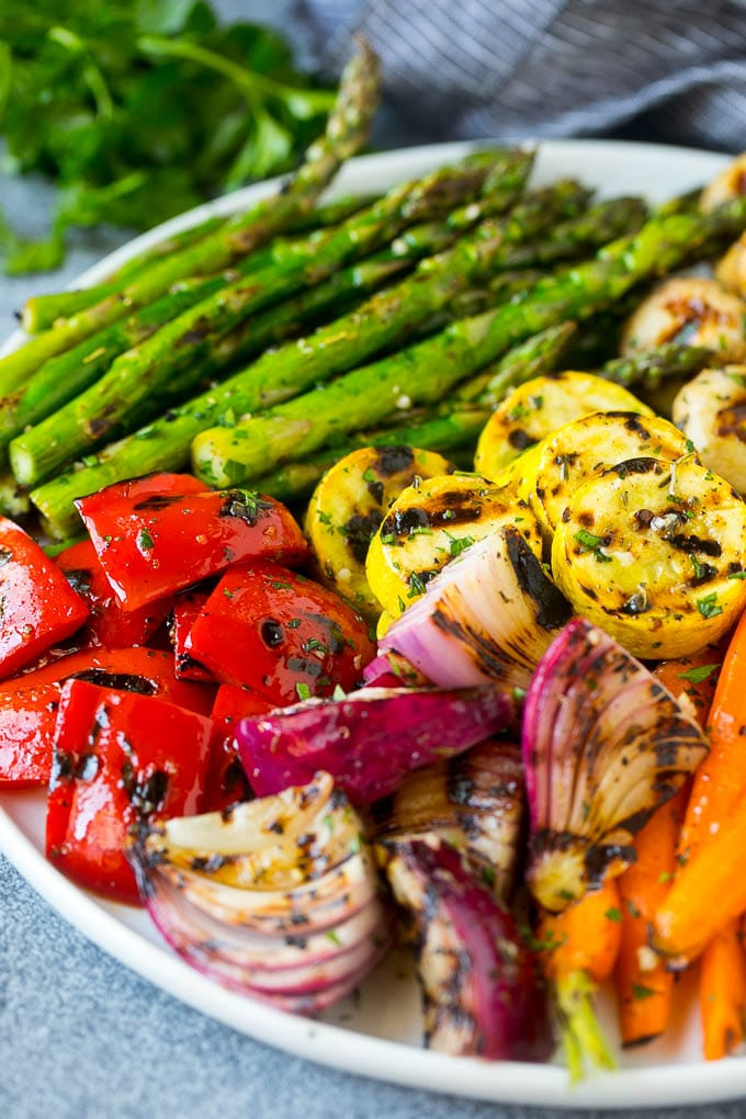 A platter of grilled veggies including peppers, onions and carrots.