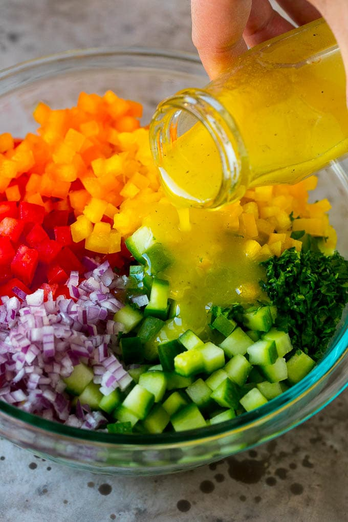 Lemon dressing being poured over chopped vegetables.