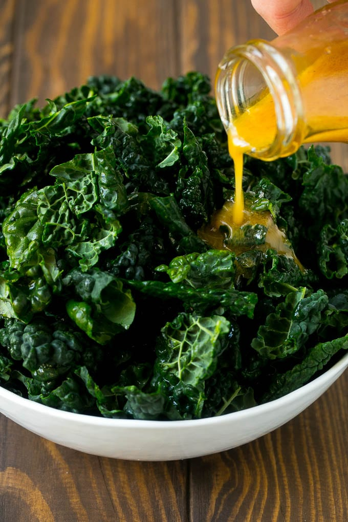 Dressing being poured over dinosaur kale leaves.