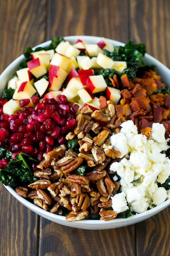 Kale salad topped with apples, bacon, pecans, pomegranate and feta cheese.