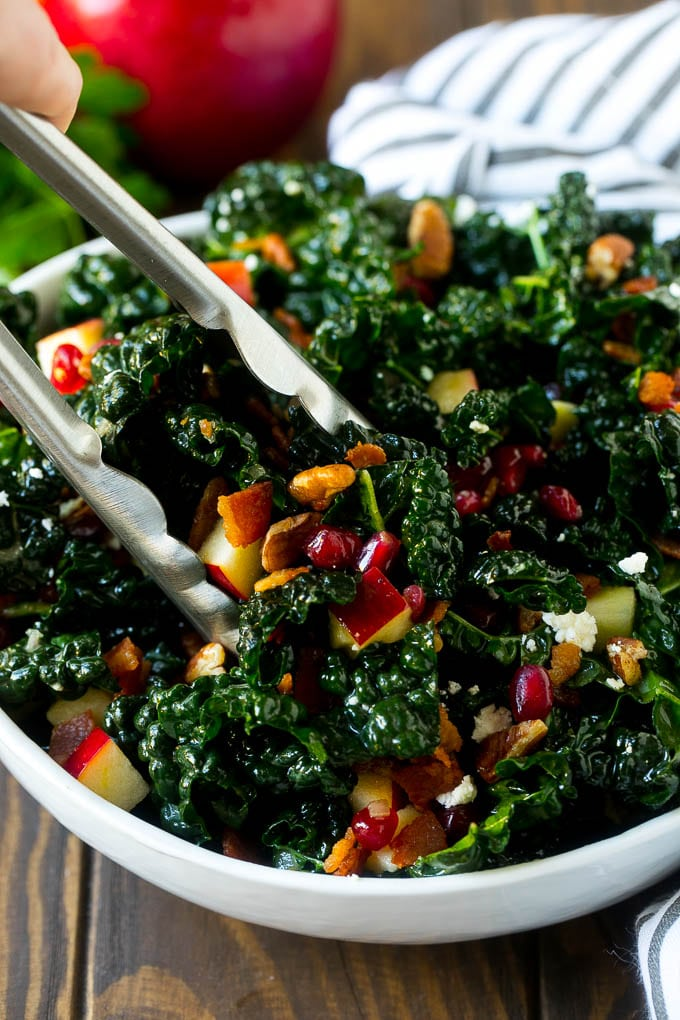 Tongs in a bowl of kale and apple salad.
