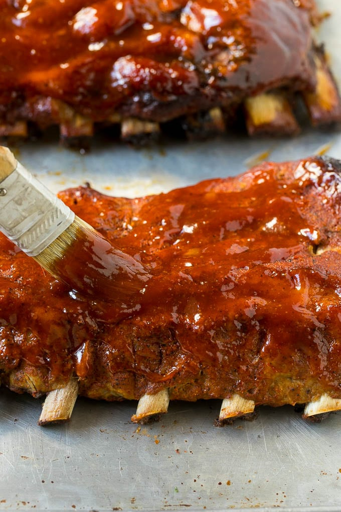 A brush coating cooked pork ribs with BBQ sauce.