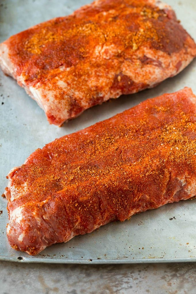 Slabs of uncooked ribs coated in BBQ spice rub.