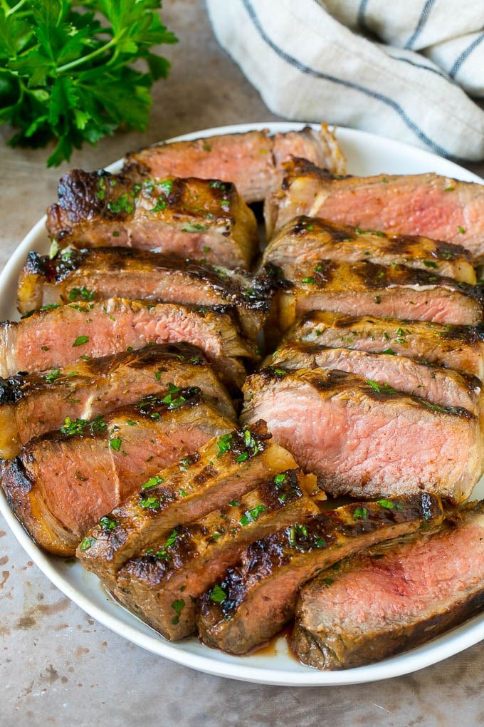 Sliced marinated steak on a serving plate.