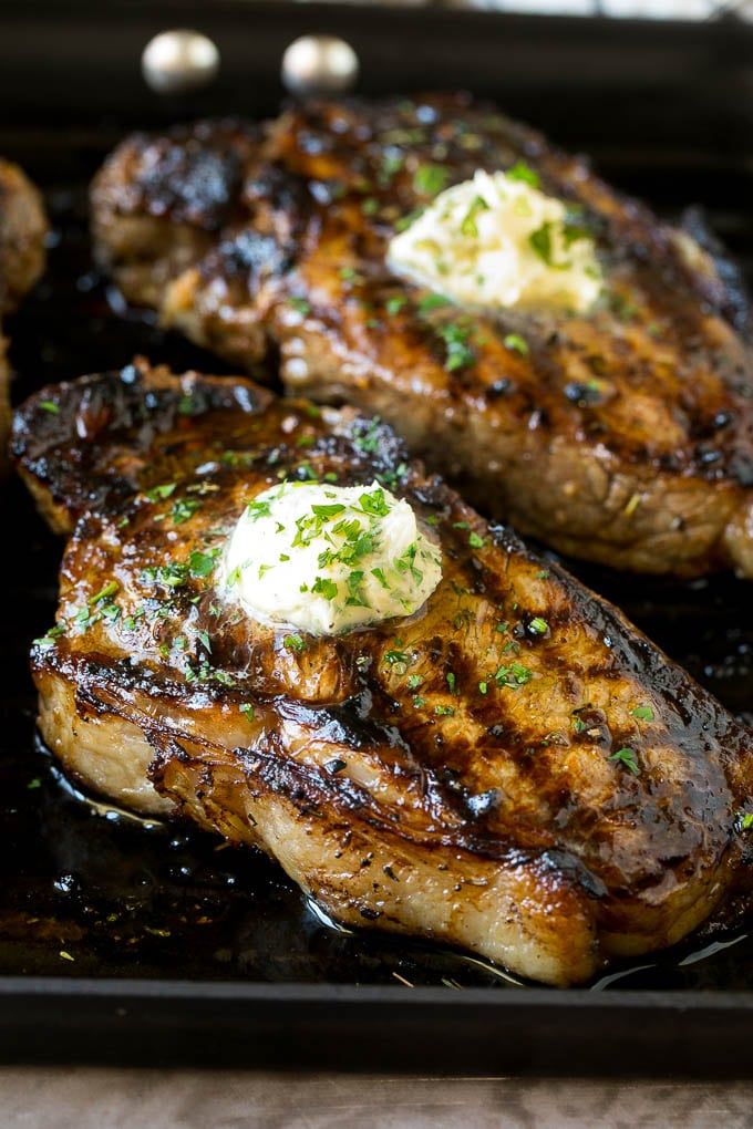 The best steak marinade with grilled steaks topped with herb butter.
