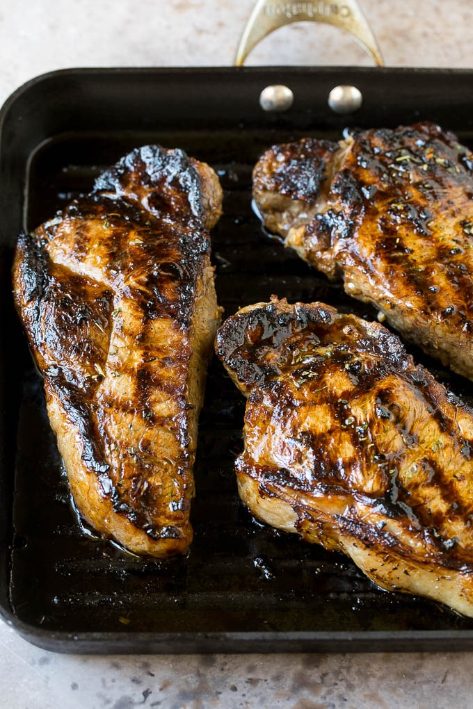 Steak marinade on New York Strip steaks in a grill pan.