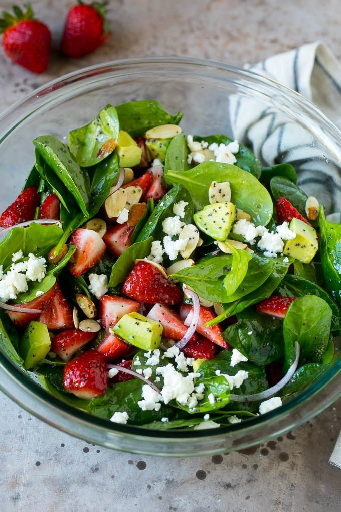 A bowl of strawberry spinach salad with feta cheese, almonds and avocado.