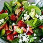 A bowl of strawberry spinach salad with poppy seed dressing, feta cheese and sliced avocado.