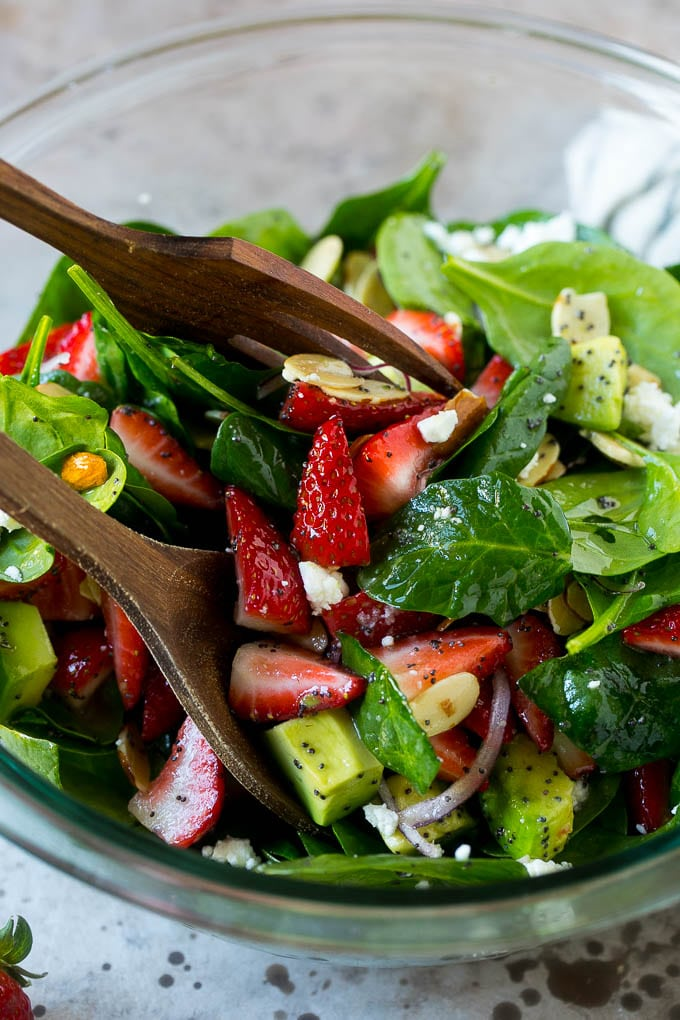 Salad tongs in a bowl of spinach salad with strawberries.