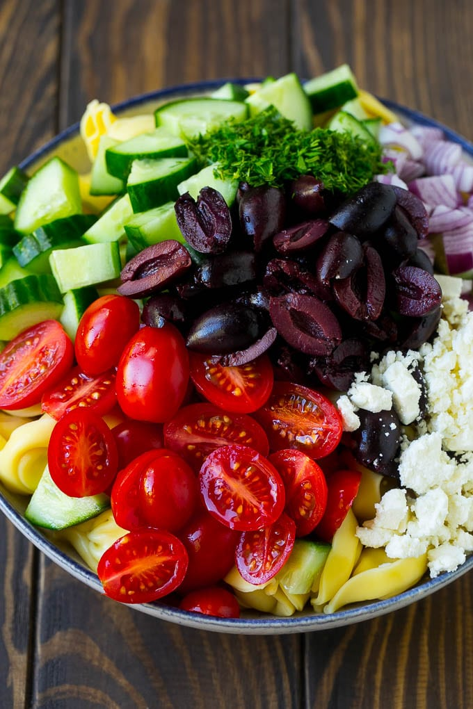 Tortellini in a bowl topped with olives, tomatoes, cucumber and feta cheese.