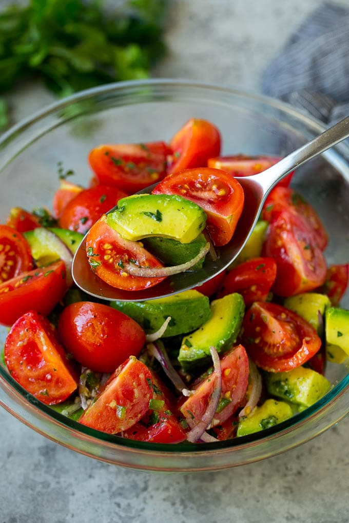 A serving spoon of tomato avocado salad in a lime dressing.