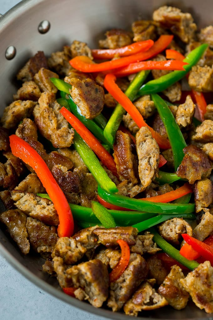 Cooked sausage and bell peppers in a pan.