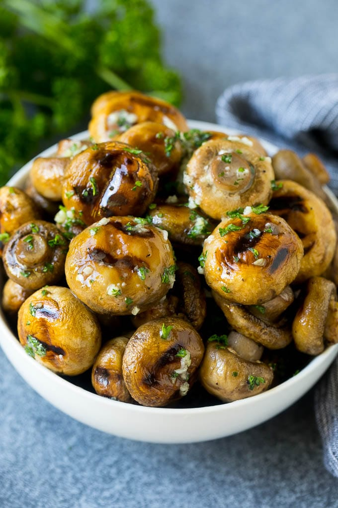 Grilled mushrooms coated with garlic butter in a serving bowl.