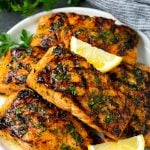 A platter of grilled salmon that's been marinated in garlic and herbs.