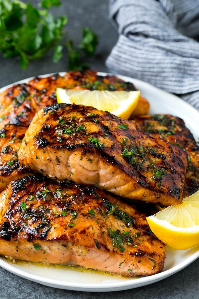 Marinated and cooked salmon garnished with lemon and herbs.
