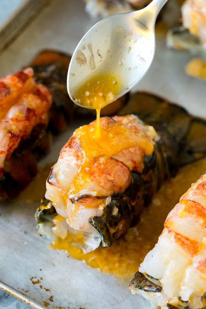 A spoon pouring garlic butter over a lobster tail.