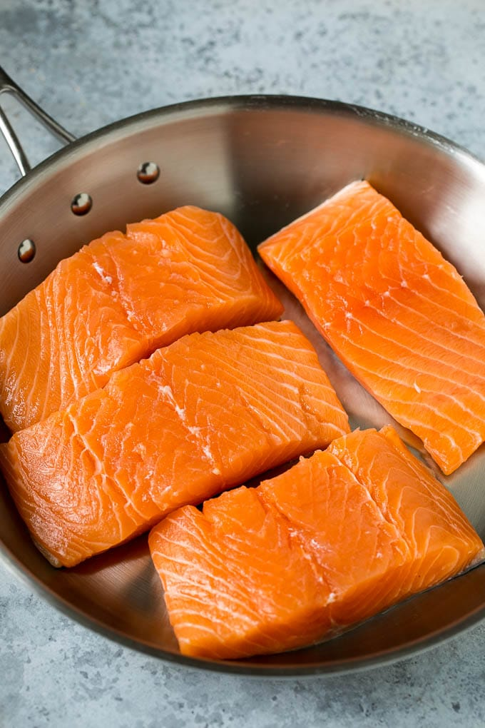 Raw salmon fillets in a pan.