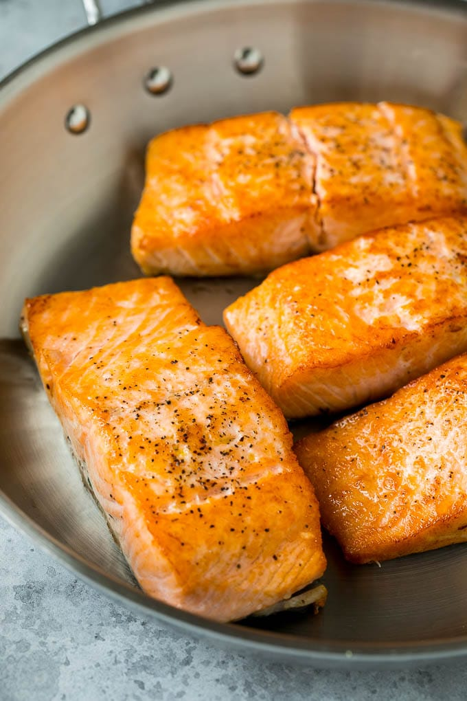 Sauteed salmon fillets in a metal skillet.