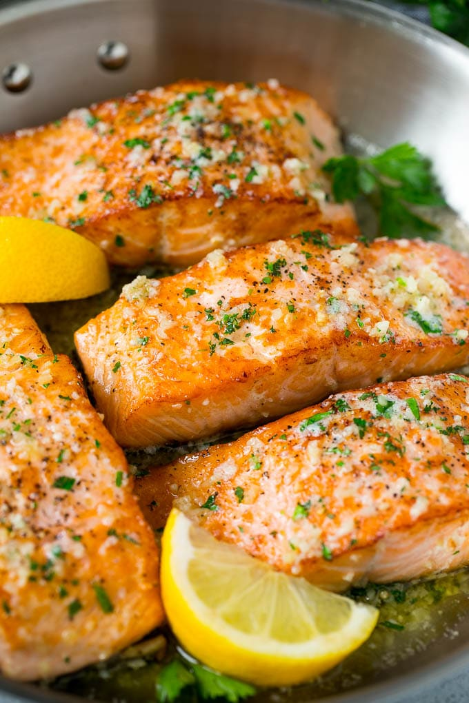 A pan of seared salmon in a butter sauce.