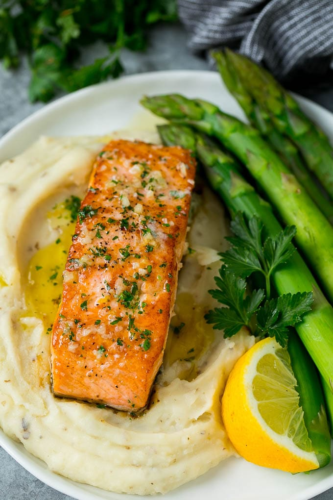 A pan seared salmon fillet served with mashed potatoes and asparagus.