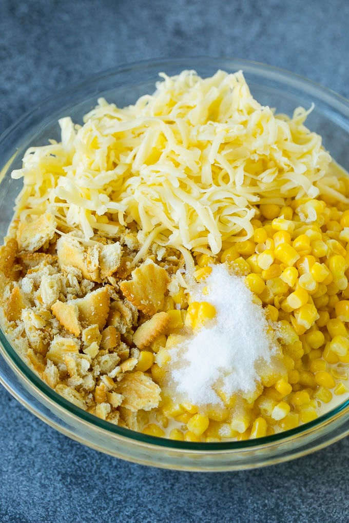 Corn, crushed crackers, seasonings and shredded cheese in a bowl.