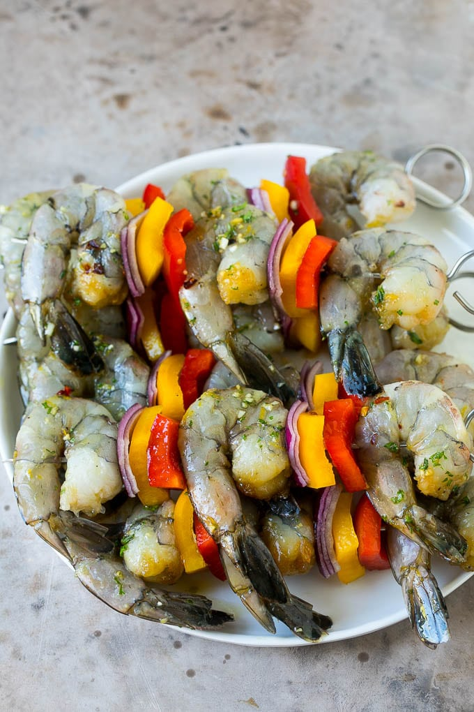 Raw shrimp on skewers with bell peppers and onions.