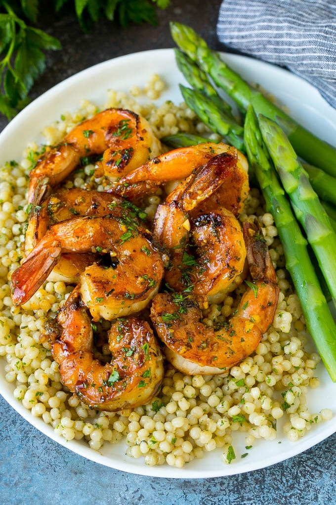 Shrimp marinade over cooked shrimp with asparagus and couscous on the side.
