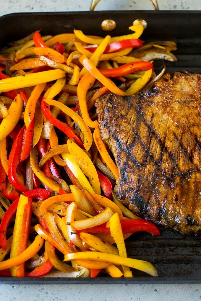 Flank steak and sliced peppers on a grill pan.