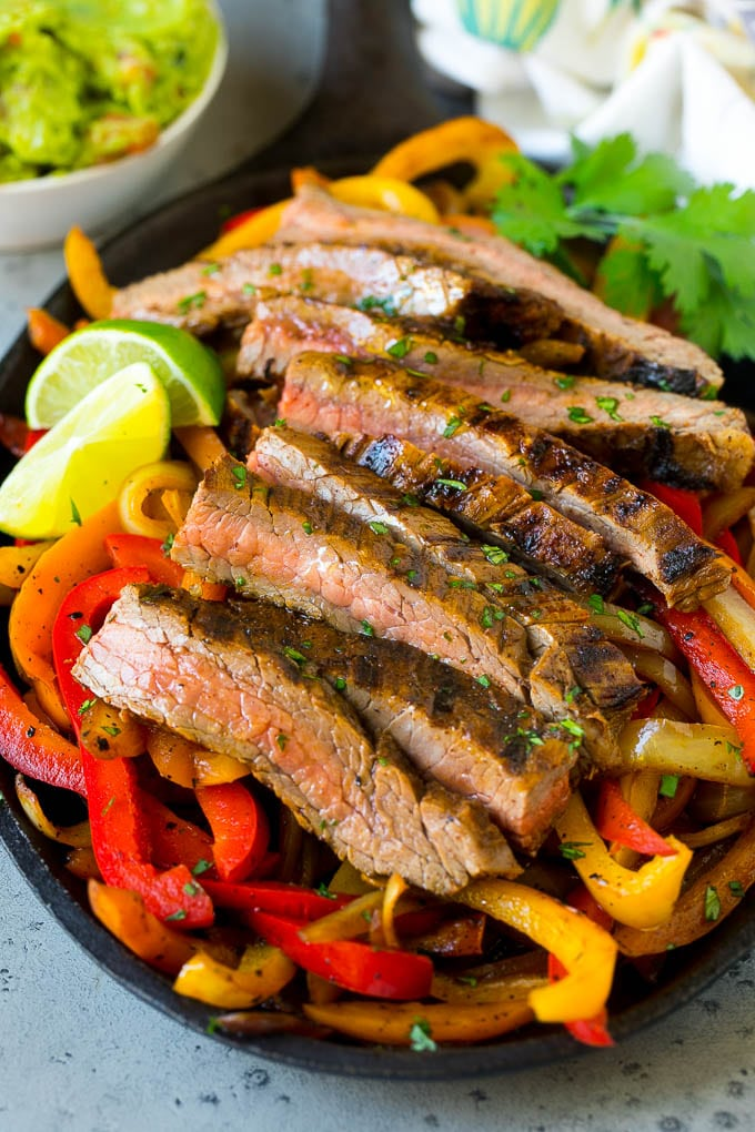 Steak fajitas served on a bed of seared peppers and onions.