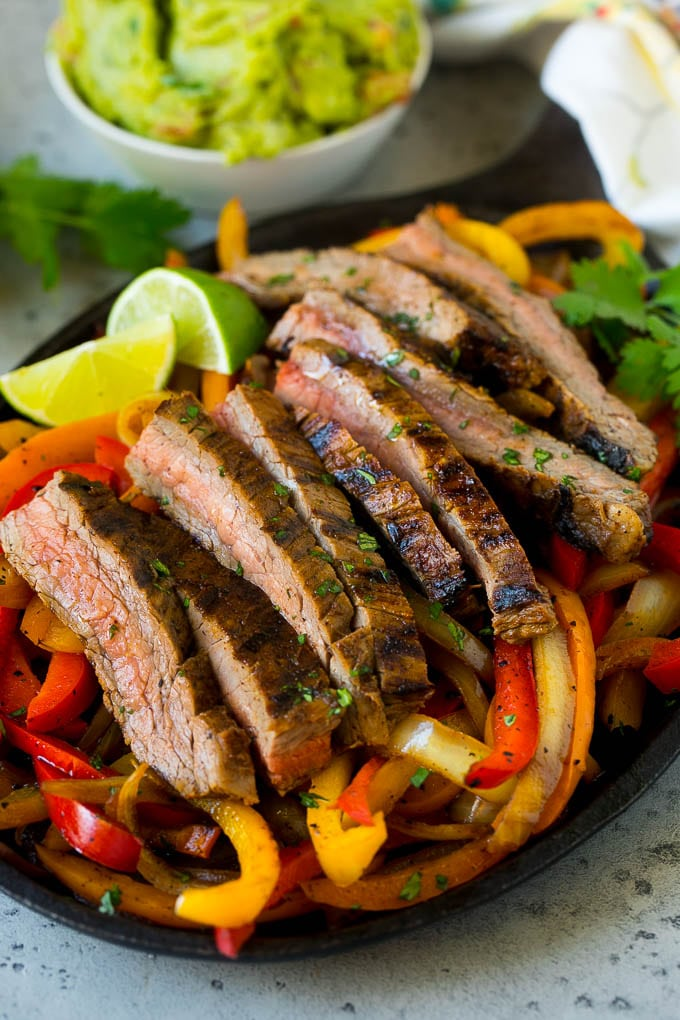 A skillet of steak fajitas with red and yellow peppers.