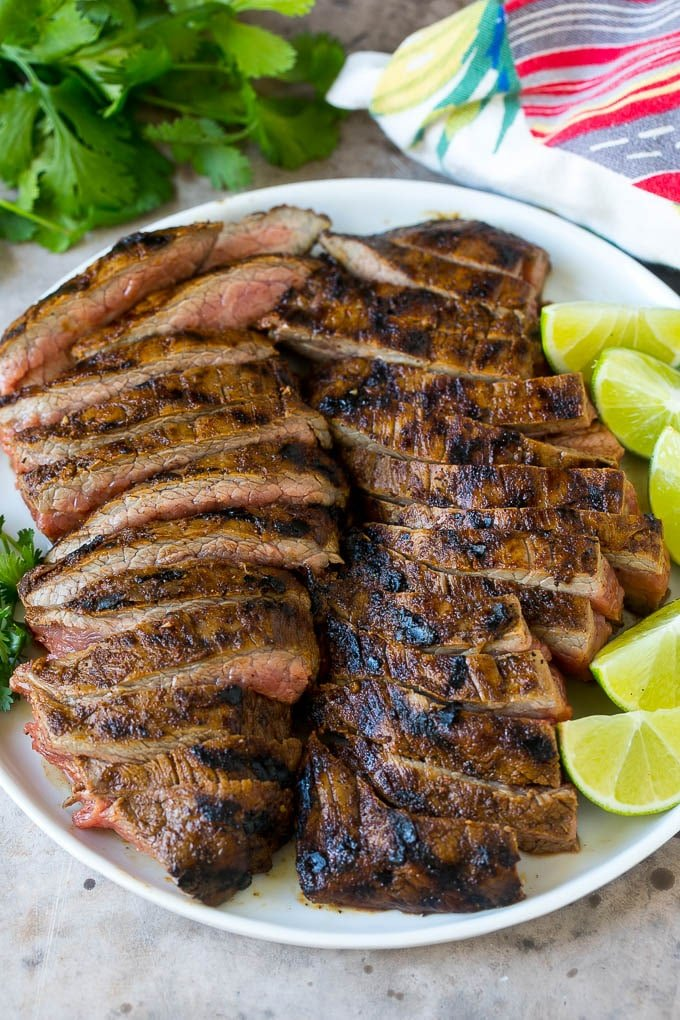 Sliced grilled flank steak on a plate.