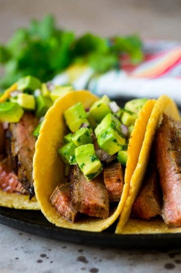 Steak tacos topped with avocado, red onion and cilantro.