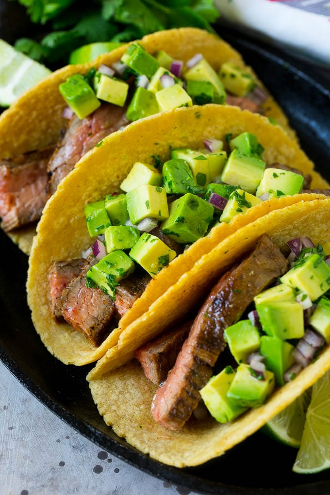 A platter of grilled steak tacos in corn tortillas.
