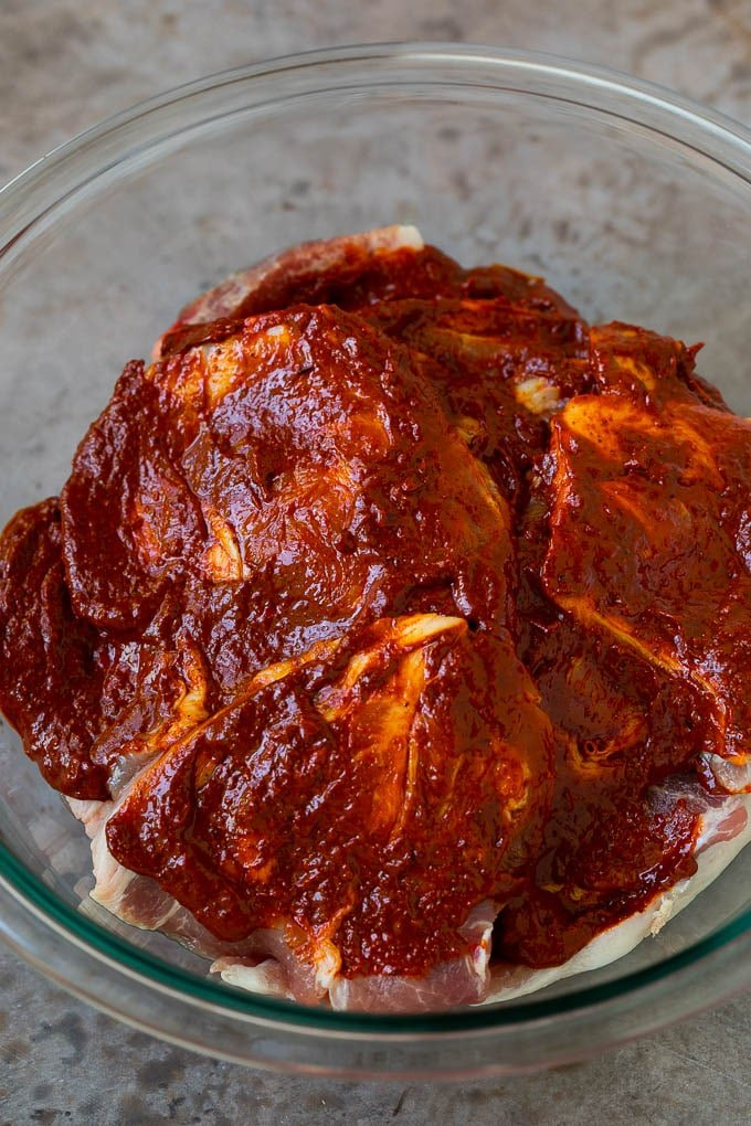 Sliced pork shoulder coated in a chile based marinade.